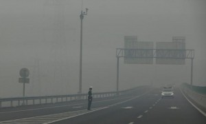 A traffic police officer standing on an expressway is barely visible due to hazardous pollution levels, in Hebei province, China, 26 November 2014. Photograph: Diego Azubel/EPA