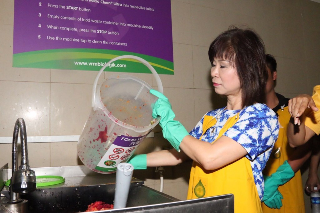 Senior Minister of State for Environment and Water Resources and Health Amy Khor participating in a demonstration of the food waste recycling system at Tiong Bahru Market. (Photo: Sherlyn Goh)